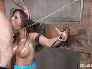 slave bound to cross on her knees has to deepthroat her master